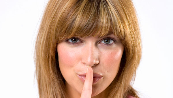 A woman with her finger to her lips symbolizing the discretion offered by Envision Medical Spa in Leduc